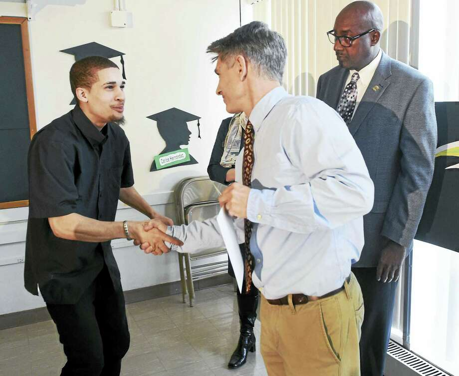 Jean  Calcano 18,  of New Haven, left, receives his graduation certificate from teacher Michael Pavano during a mid-year commencement exercises for seven students at the New Light High School in New Haven  on Jan. 22. At right is New Light High School Principal Larry Canaway. Photo: (Peter Hvizdak - New Haven Register)   / ©2016 Peter Hvizdak