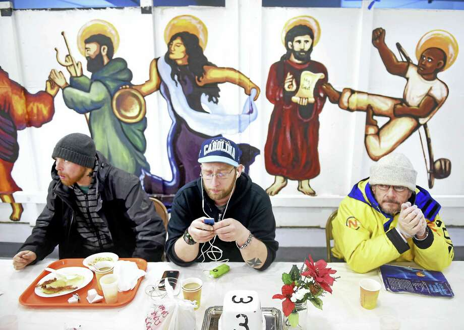 From left, Pete Pizzillo, Jason DeMasi and Gabor Kovacs have breakfast at the Sunrise Cafe in the basement of the St. Paul and St. James Episcopal Church in New Haven Friday. Photo: ARNOLD GOLD — NEW HAVEN REGISTER