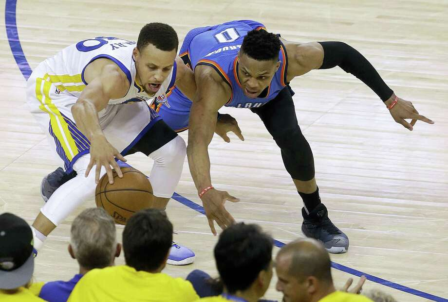 Warriors guard Stephen Curry, left, is defended by the Thunder's Russell Westbrook during the second half on Monday. Photo: Jeff Chiu — The Associated Press   / AP