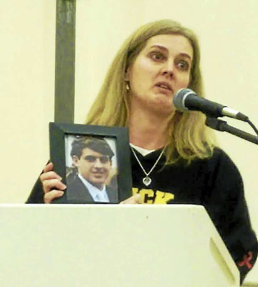 Sue Kruczek of Guilford, who lost her son to a drug overdose, holds his photo as she speaks to the crowd at the Guilford Community Center Tuesday. Photo: HENRY CHISHOLM — NEW HAVEN REGISTER