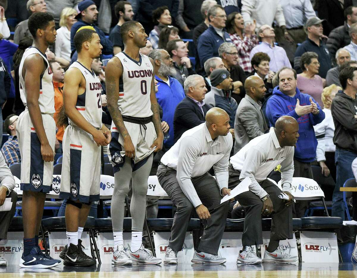 Connecticut players and coaches watch Cincinnati's game-winning free throw during Cincinnati's 58-57 victory in an NCAA college basketball game in Hartford, Conn., on Thursday, Jan. 28, 2016. (AP Photo/Fred Beckham)