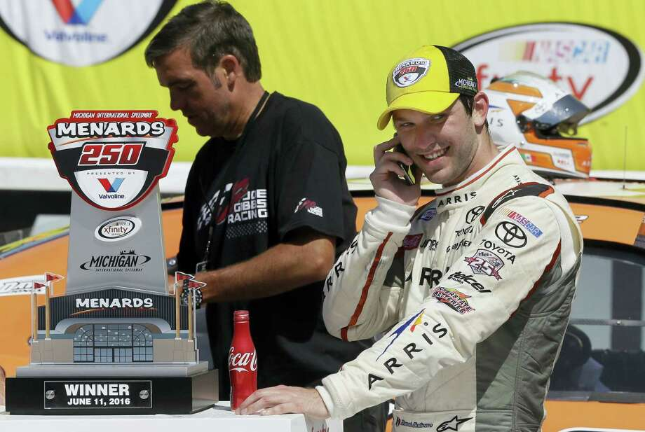 Daniel Suarez takes a phone call after winning the NASCAR Xfinity series race at Michigan International Speedway on Saturday. Photo: Carlos Osorio — The Associated Press   / AP