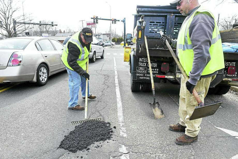 Michael Lang (left) and Joe Zito of the East Haven Public Works Department patch a pothole on Forbes Place in East Haven Friday. Photo: (Arnold Gold-New Haven Register)