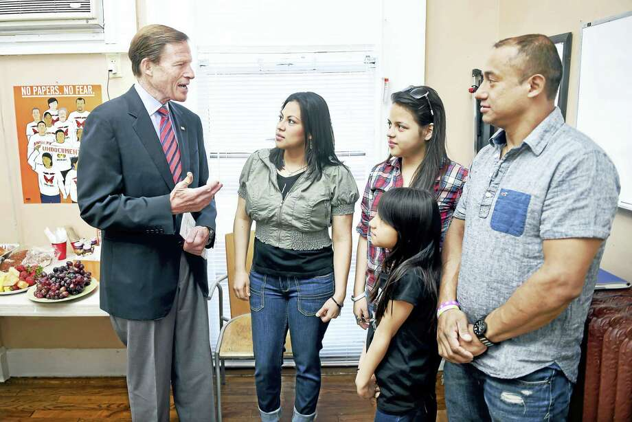 U.S. Senator Richard Blumenthal (left) talks with Ana Lucero Castillo (center), Isaias Olivares (right) and their children, Naamy, 13, and Melanie, 9, at Junta for Progressive Action in New Haven on 4/17/2016. The family plans to join thousands of others outside of the U.S. Supreme Court during oral arguments challenging the DAPA and DACA programs. Photo: Arnold Gold — New Haven Register