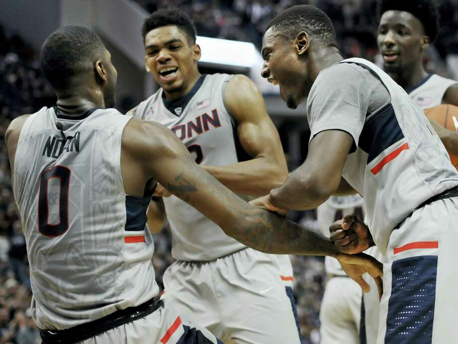 Connecticut's Sterling Gibbs, right, and Shonn Miller, center, celebrate as they help up Connecticut's Phillip Nolan during Saturday's win against Georgetown. The Huskies hope to keep that momentum going against Cincinnati. Photo: Jessica Hill — The Associated Press   / FR125654 AP