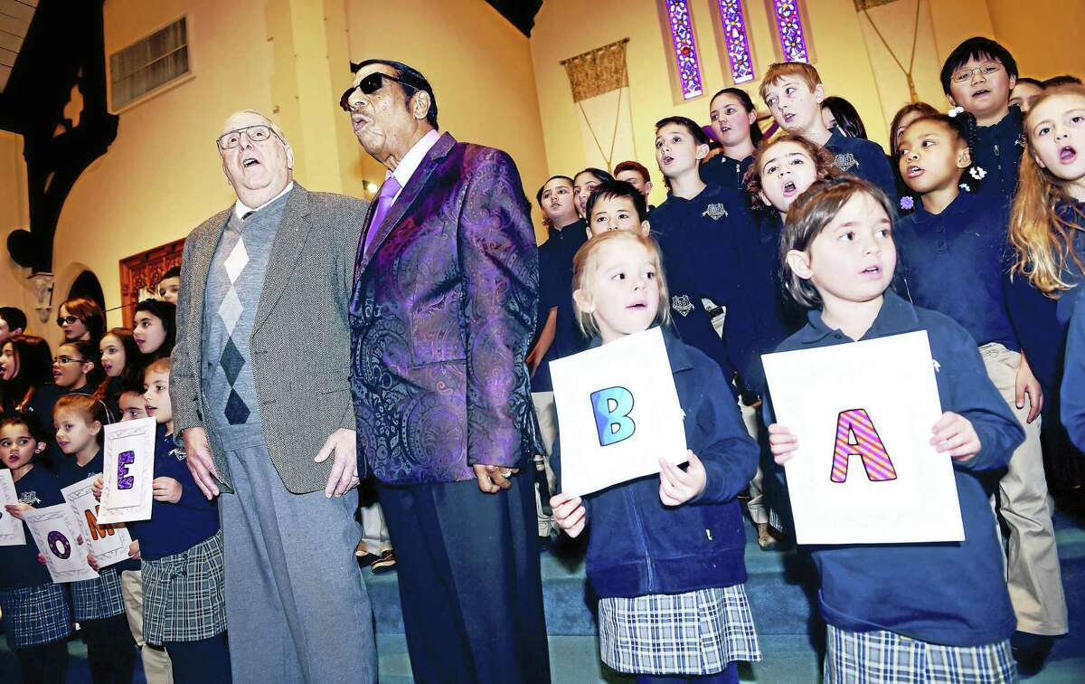"""ARNOLD GOLD — NEW HAVEN REGISTER Vinnie Mazzetta, far left, and Fred Parris, left, leader of the Five Satins, sing """"In the Still of the Night"""" with St. Bernadette School students in the church sanctuary Monday. The Five Satins recorded the song in the church basement on Feb. 19, 1956. Mazzetta played saxophone during the recording."""