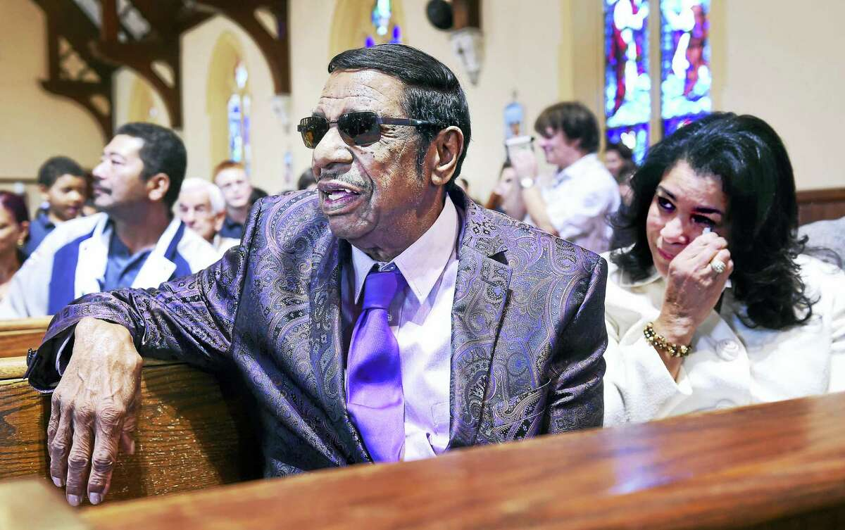 """ARNOLD GOLD — NEW HAVEN REGISTER Fred Parris, left, leader of the Five Satins, listens to St. Bernadette School students sing """"In the Still of the Night"""" in the church sanctuary as his wife, Emma, sheds a tear Monday."""