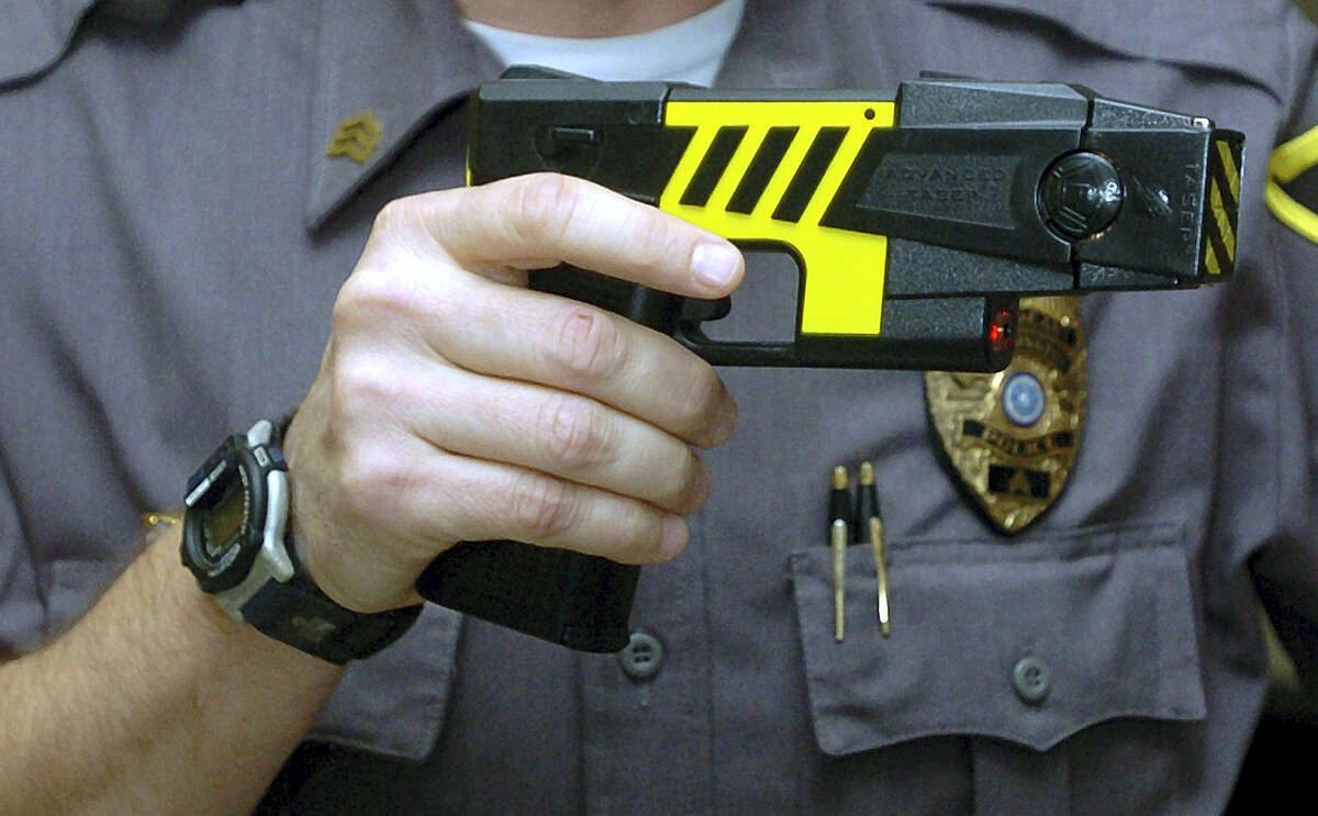 In this Oct. 28, 2004 photo, an officer holds a stun gun used by his police department in a Farmington, Conn. Police across Connecticut disproportionately fired stun guns at blacks and Hispanics in 2015 while whites were the main beneficiaries when officers only threatened to use the weapons, according to preliminary data from the nation's first accounting by a state of law enforcement stun gun use.