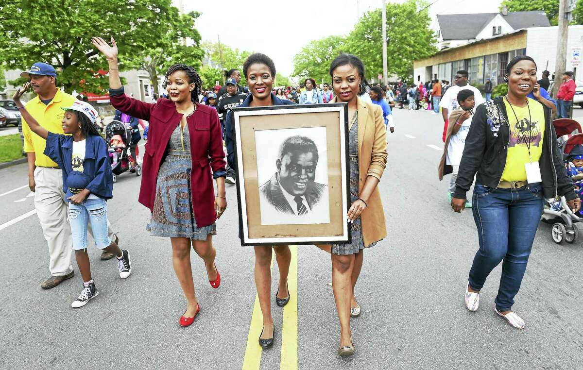 (Arnold Gold-New Haven Register) Left to right, Jackie Robinson's granddaughters Faith, Rahelie and Rachel Robinson of Tanzania march in the Freddy Fixer Parade on Dixwell Avenue in New Haven Sunday, carrying a portrait of their grandfather.