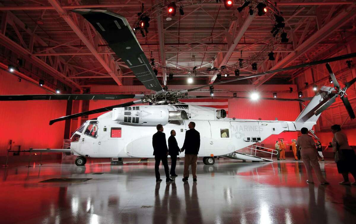 In this May 5, 2014 photo, attendees look at the newly unveiled Sikorsky CH-53K heavy lift helicopter during an official rollout at the Sikorsky Aircraft Corporation in Jupiter, Fla.
