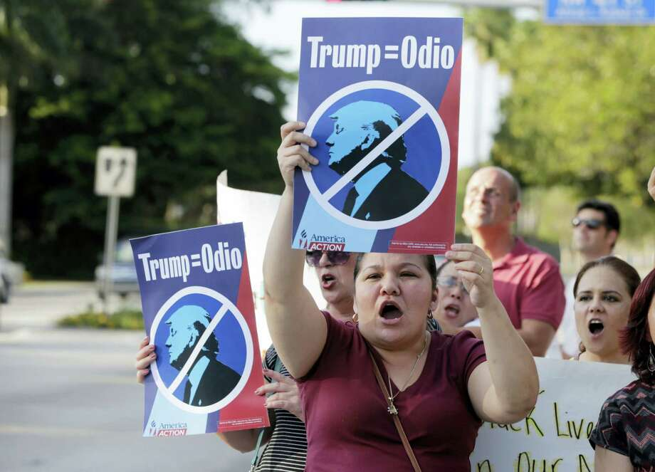 """Berta Sandes, 38, of Miami, an undocumented immigrant from Nicaragua, holds a sign which translates to """"Trump Equals Hate"""" during a protest against Republican presidential candidate Donald Trump outside of the Trump National Doral golf resort, March 14 in Doral, Fla. Photo: File Photo   / AP"""