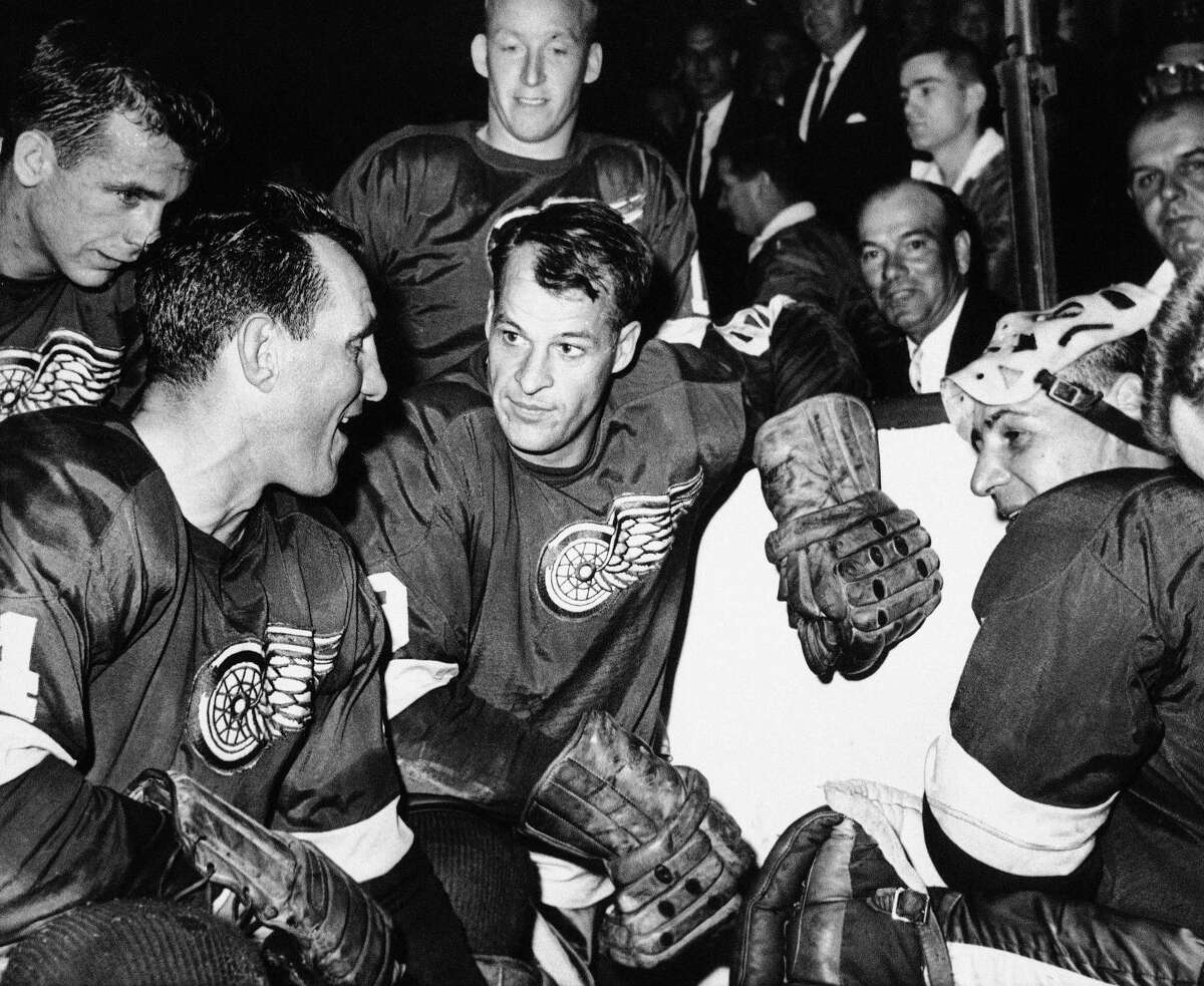 In this 1963 file photo, Detroit Red Wings star forward Gordie Howe is surrounded by teammates as he kneels after scoring his 544th goal to tie the National Hockey League all-time record.