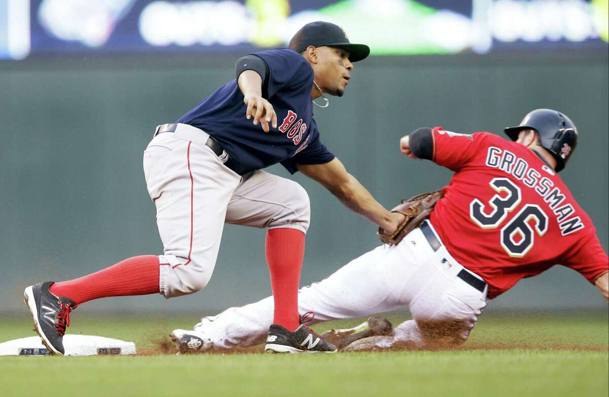 The Twins' Robbie Grossman, right, is tagged out by Red Sox shortstop Xander Bogaerts on a steal attempt on Friday.