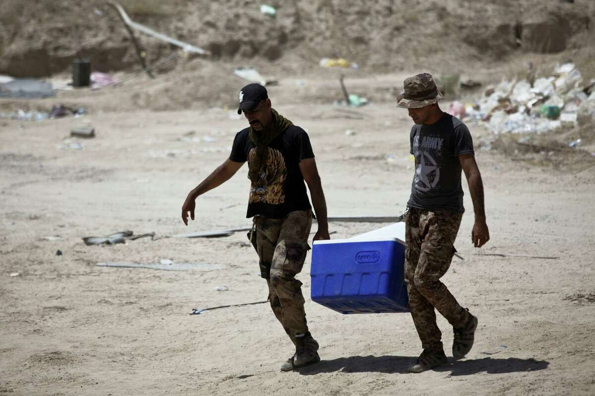 In this Tuesday, June 7, 2016, file photo, Iraqi counterterrorism forces carry ice on a scorching day on their front line position during an operation to oust Islamic State militants from Fallujah, Iraq on the first day of Ramadan. The fight to retake the Islamic State-held city of Fallujah is continuing into Ramadan, and both sides say the Muslim holy month gives their military cause a greater significance. While Iraq's most influential Shiite cleric says fighters do not need to fast if they believe it will compromise their abilities on the battlefield, many Iraqi troops say they plan to so despite the harsh conditions and the summer heat.