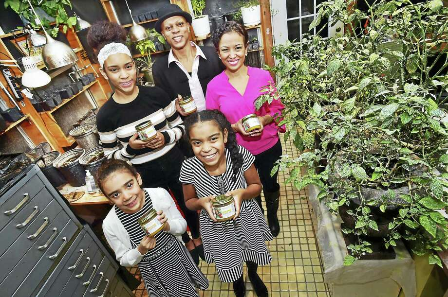 George Clermont, his wife, Brunilda, and three daughters, Cassandra, 8, Gabriella, 14, and Adrienne, 10, pause in their New Haven home growing room holding Piman-Cho!, mango and pineapple salsa made from the family heirloom of Haitian hot peppers. Photo: Catherine Avalone — New Haven Register     / New Haven RegisterThe Middletown Press