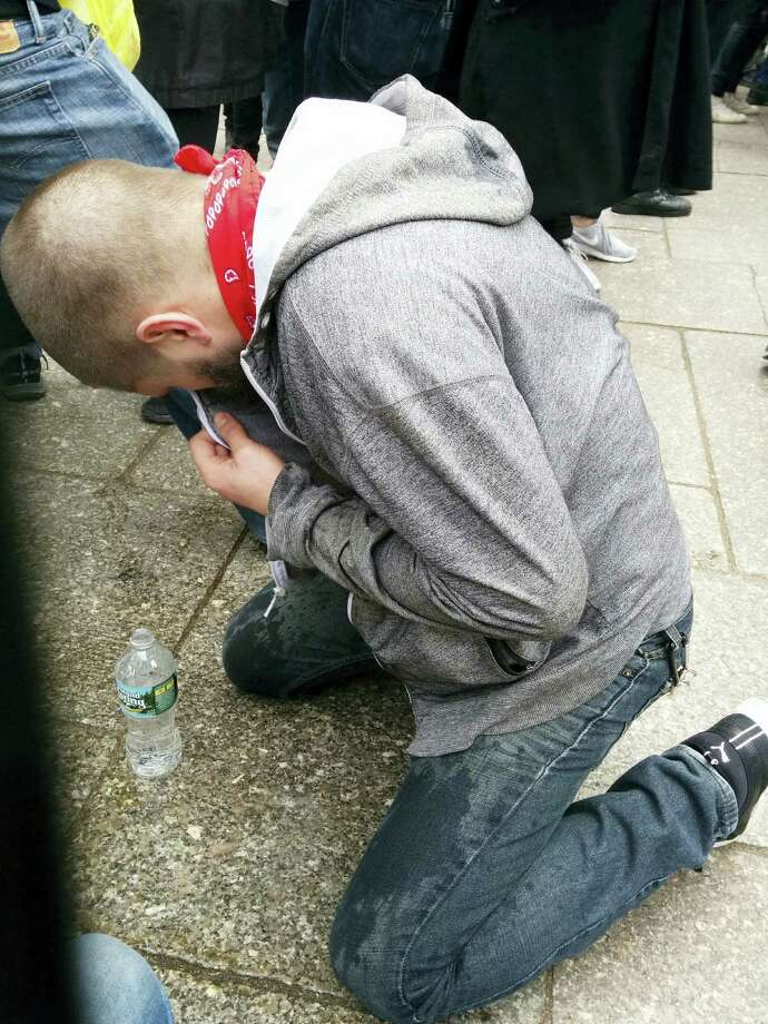 Alex Renner washes his eyes out with bottled water at the scene of a protest against Republican presidential hopeful Donald Trump, Saturday, March 19, 2016 in New York. Renner said that he was hit with pepper spray as protestors collided with police. Photo: AP Photo — Julie Walker / Copyright 2016 The Associated Press. All rights reserved. This material may not be published, broadcast, rewritten or redistributed without permission.