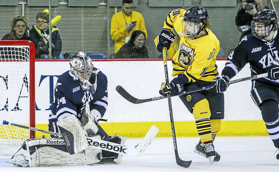 Yale goaltender Alex Lyon makes save against Qunnipiac earlier this season. Lyon won the Dryden Award as the top goalie in ECAC Hockey. Photo: John Vanacore — For The Register   / (c)John H.Vanacore/Register