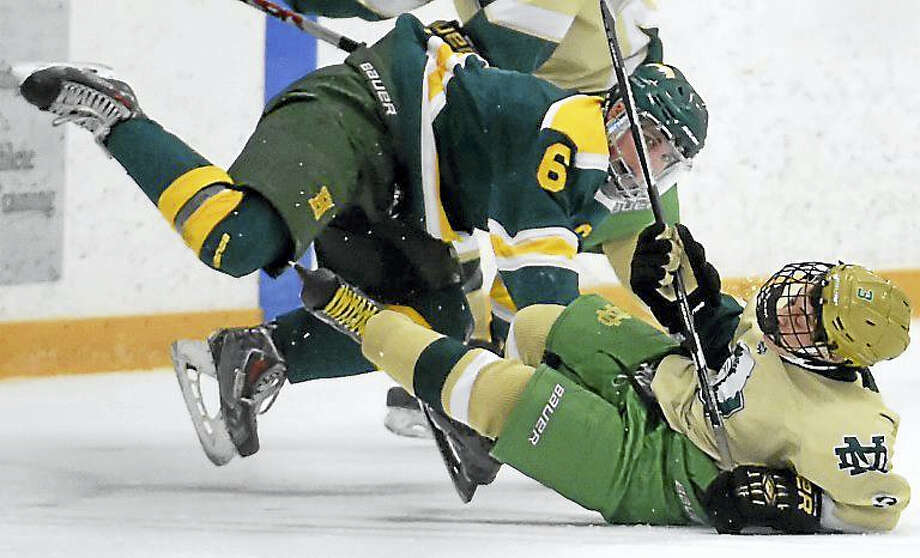 Hamden's Christian Ugolik and Ian Hayden of Notre Dame-West Haven take a tumble during first period hockey action Monday at Bennett Rink in West Haven. Photo: Peter Hvizdak – New Haven Register   / ?2016 Peter Hvizdak
