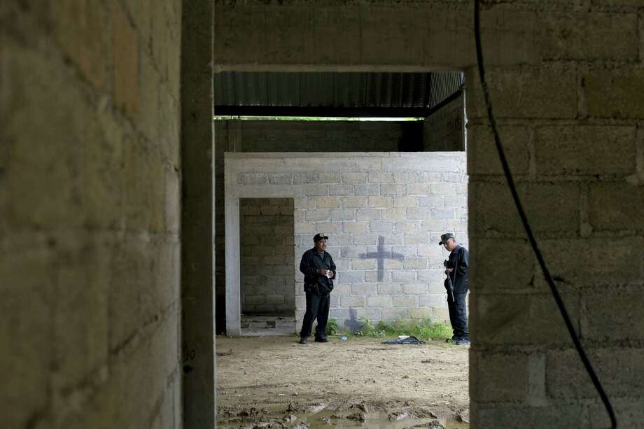 In this July 3, 2014, file photo, state police stand inside a warehouse where a black cross marks a wall near blood stains on the ground, after a shootout between Mexican soldiers and alleged criminals in Tlatlaya, Mexico. Photo: AP Photo — Rebecca Blackwell, File / AP