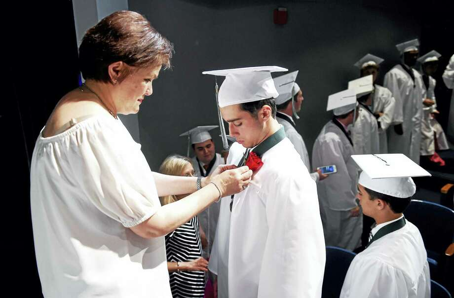 Anna Pesce, left, pins a rose on Austin Aitro before commencement exercises for Hamden Hall Country Day School in Hamden Friday. Photo: Arnold Gold — New Haven Register