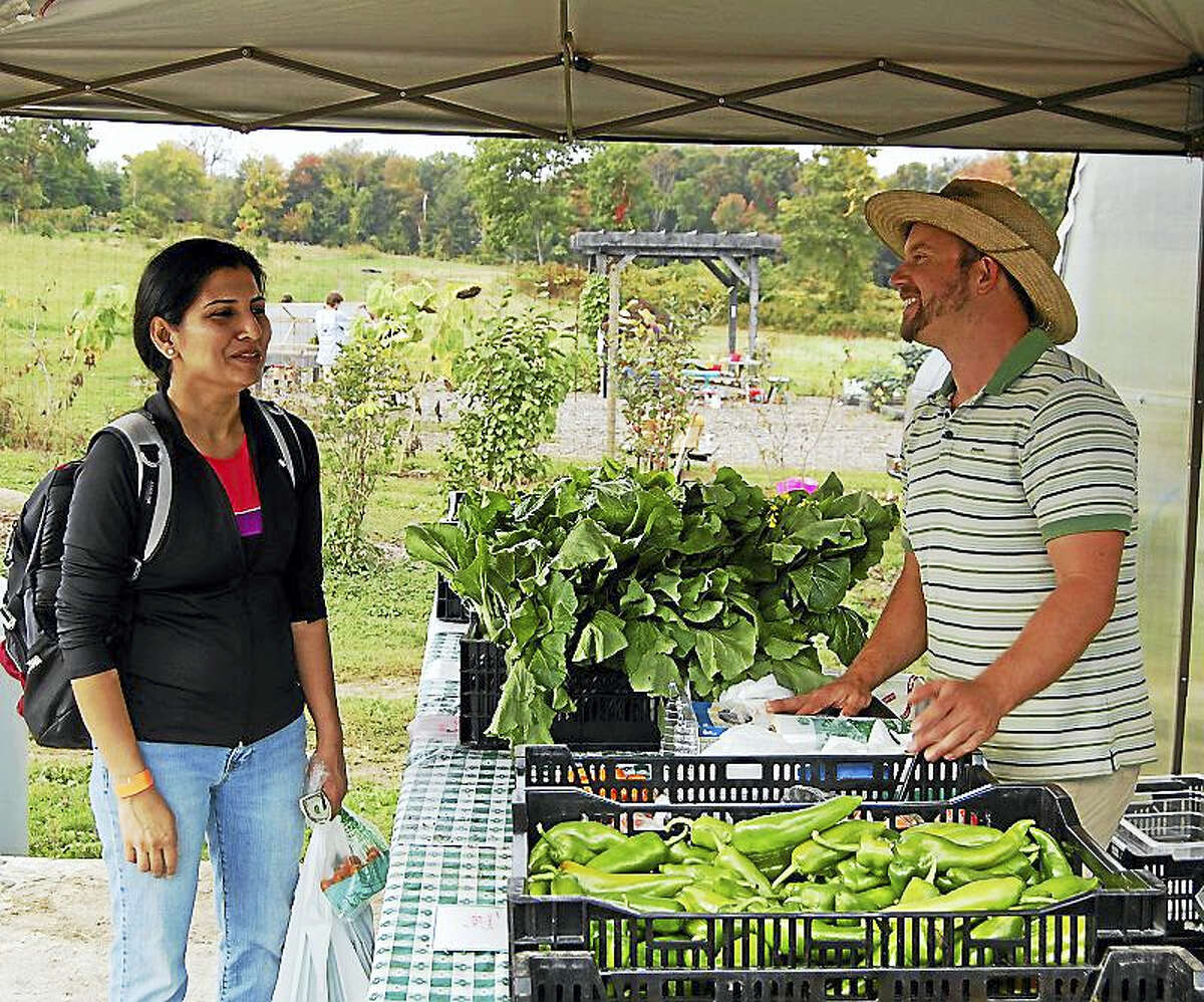 """Steve Munno, know as """"Farmer Steve"""" at Massaro Community Farm in Woodbridge, talks to a customer who's buying produce during the farm's annual Family Fun Day."""
