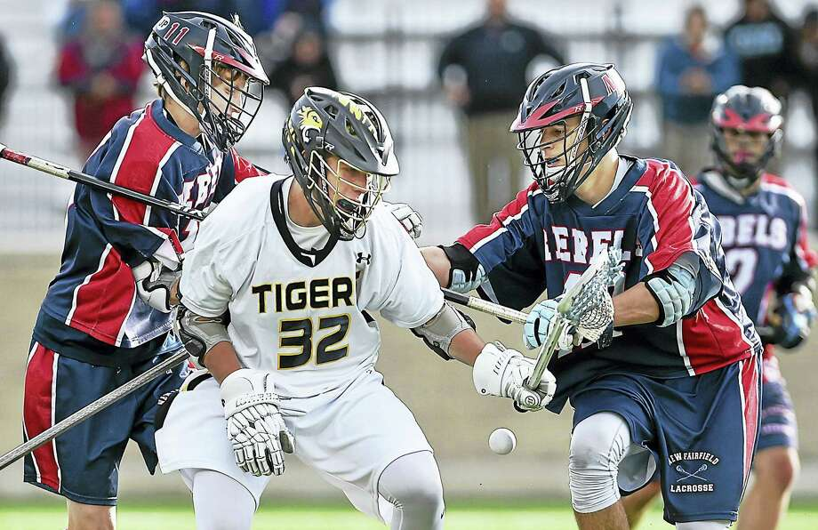 Hand's Nate Palumbo (32, center) is defended by two New Fairfield players during the Class M semifinal game at Rafferty Stadium at Fairfield University. Photo: Catherine Avalone — New Haven Register   / New Haven RegisterThe Middletown Press