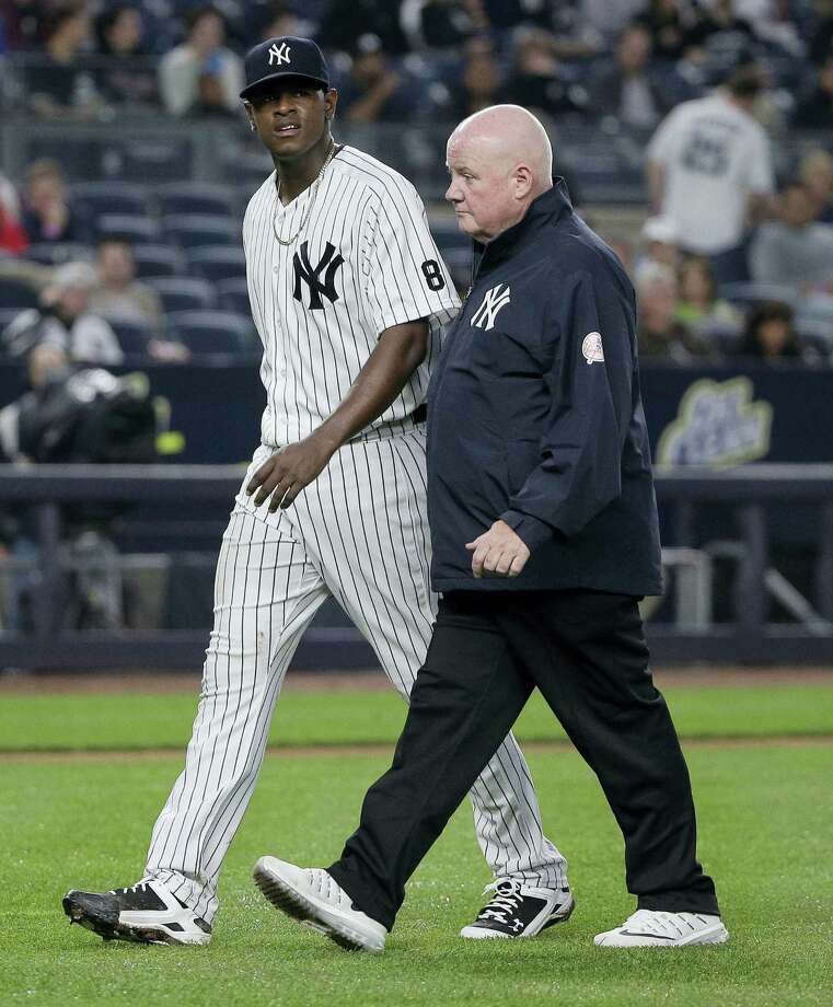 Yankees pitcher Luis Severino, left, walks off the field with head trainer Steve Donohue after giving up a two-run home run against the White Sox on Friday. Photo: Julie Jacobson — The Associated Press   / Copyright 2016 The Associated Press. All rights reserved. This material may not be published, broadcast, rewritten or redistribu