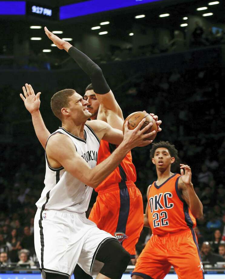Brooklyn Nets center Brook Lopez (11) runs into Oklahoma City Thunder center Enes Kanter (11) as he goes up for a layup in the second half Sunday. Lopez finished with 31 points. Photo: The Associated Press   / AP