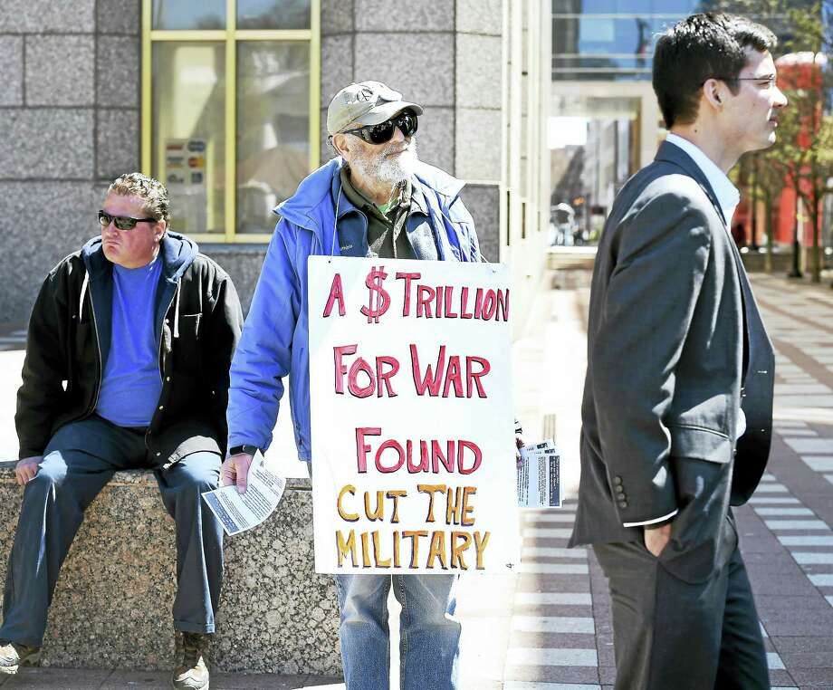 Henry Lowendorf, center, of the Greater New Haven Peace Council hands out leaflets highlighting the percentage of tax dollars used for military expenditures, on Church Street in New Haven Friday. Photo: Arnold Gold — New Haven Register