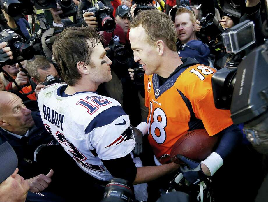 New England Patriots quarterback Tom Brady, left, and Denver Broncos quarterback Peyton Manning after the Broncos defeated the Patriots 20-18 Sunday to advance to Super Bowl. Photo: David Zalubowski – The Associated Press   / AP