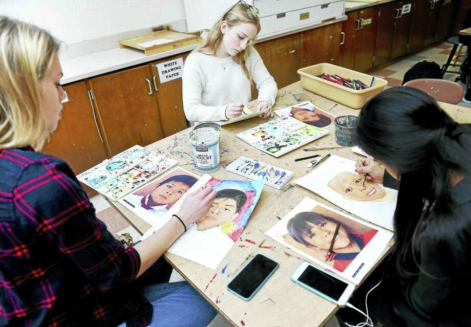 Left to right, Hannah Smith, 18, Cassidy Marry, 16, and Neha Pashankar, 16, create portraits of orphaned and disadvantaged children from Bolivia as part of The Memory Project during honors art class at Amity High School in Woodbridge on Monday. . Photo: (Arnold Gold-New Haven Register)