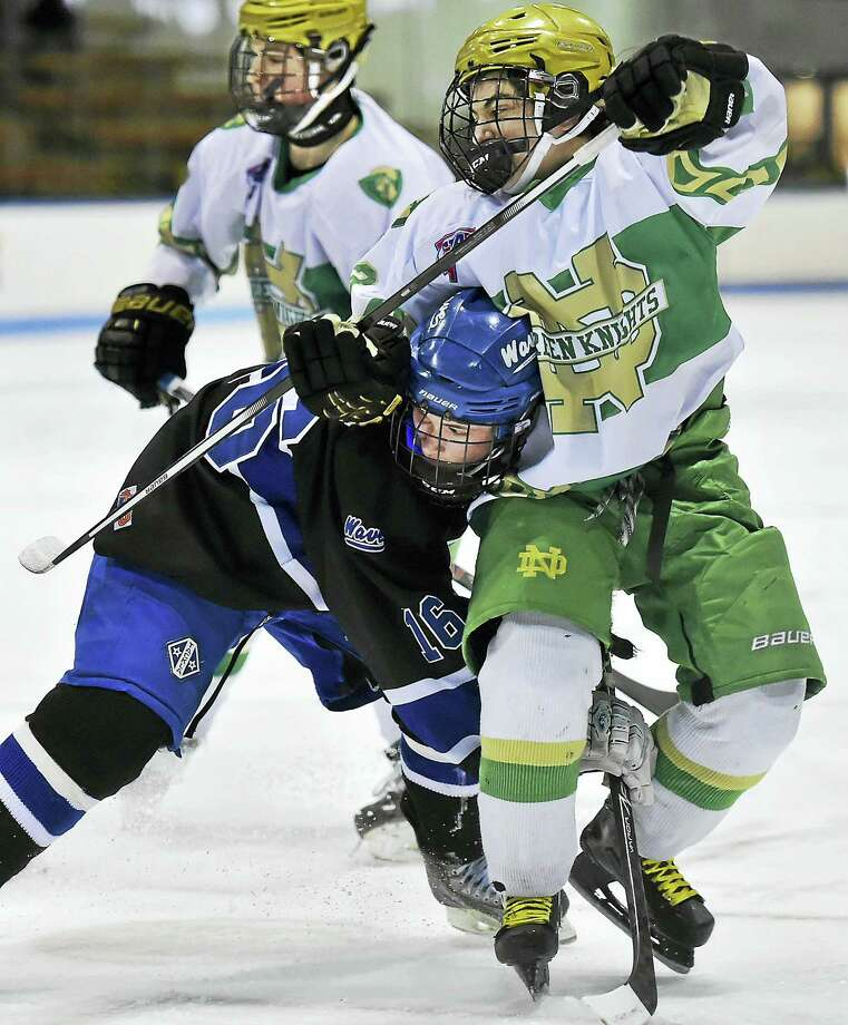 Notre Dame-West Haven's Ian Hayden battles Darien's Jay Dickson in the first period of CIAC Division 1 semifinal action, Wednesday, March 16, 2016, at Ingalis Rink in New Haven. Photo: Catherine Avalone — New Haven Register   / New Haven RegisterThe Middletown Press