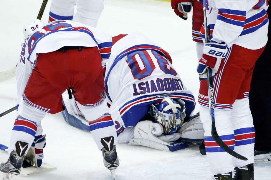 Rangers goalie Henrik Lundqvist (30) kneels on the ice after getting a stick to the face during the first period on Wednesday. Photo: Gene J. Puskar — The Associated Press   / Copyright 2016 The Associated Press. All rights reserved. This material may not be published, broadcast, rewritten or redistributed without permission.