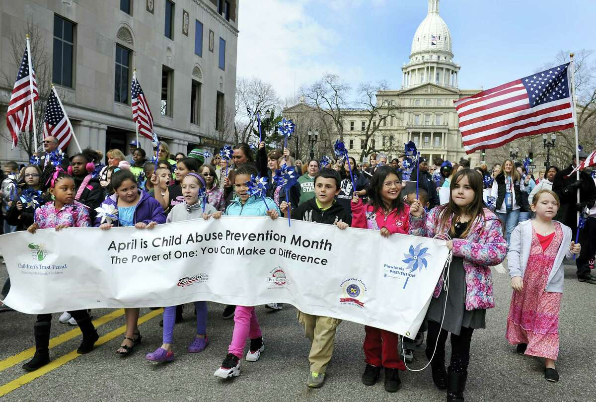 In this April 16, 2013 photo, schoolchildren lead the way carrying pinwheels during part of the Children's Trust Fund prevention awareness day rally event to prevent child abuse and neglect in Lansing, Mich. The pinwheel is the national symbol for child abuse prevention. The United States lacks coherent, effective strategies for reducing the stubbornly high number of children who die each year from abuse and neglect, a commission created by Congress reported Thursday, March 17, 2016, after two years of sometimes divisive deliberations.
