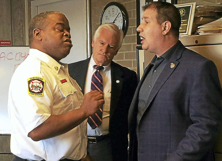 New Haven Fire Chief Ralph Black, left, and IAFF Local 825 President Frank Ricci got into a heated discussion Wednesday at a ceremony to promote Antonio Almodovar to director of training. At center in photo is Fire Commissioner William Celentano. Photo: Wes Duplantier — The New Haven Register