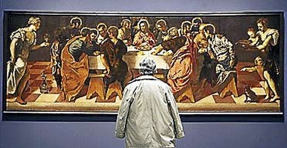"In this file photo, a visitor to Madrid's El Prado museum looks at Tintoretto's ""The Last Supper."" Photo: Emilio Naranjo/AP"
