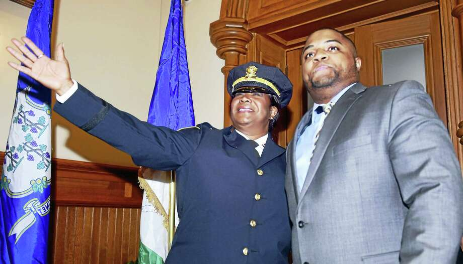 New Haven Police Capt. Patricia Helliger waves to the crowd in attendance for her promotion ceremony at City Hall in New Haven Friday. At right is her nephew, Alex Brooks, who pinned Helliger with a captain's badge. Photo: ARNOLD GOLD — NEW HAVEN REGISTER