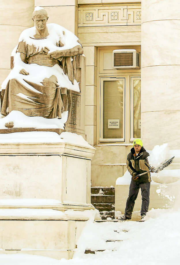 John Vanacore/Register  Nick Poulin shovels the steps of the federal courthouse in New Haven in the aftermath of the winter storm Sunday morning. Photo: Journal Register Co. / John Vanacore-Register