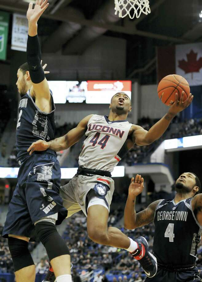 UConn's Rodney Purvis shoots between Georgetown's Bradley Hayes, left, and D'Vauntes Smith-Rivera, right, in the first half Saturday in Hartford. Photo: Jessica Hill — The Associated Press   / AP2016