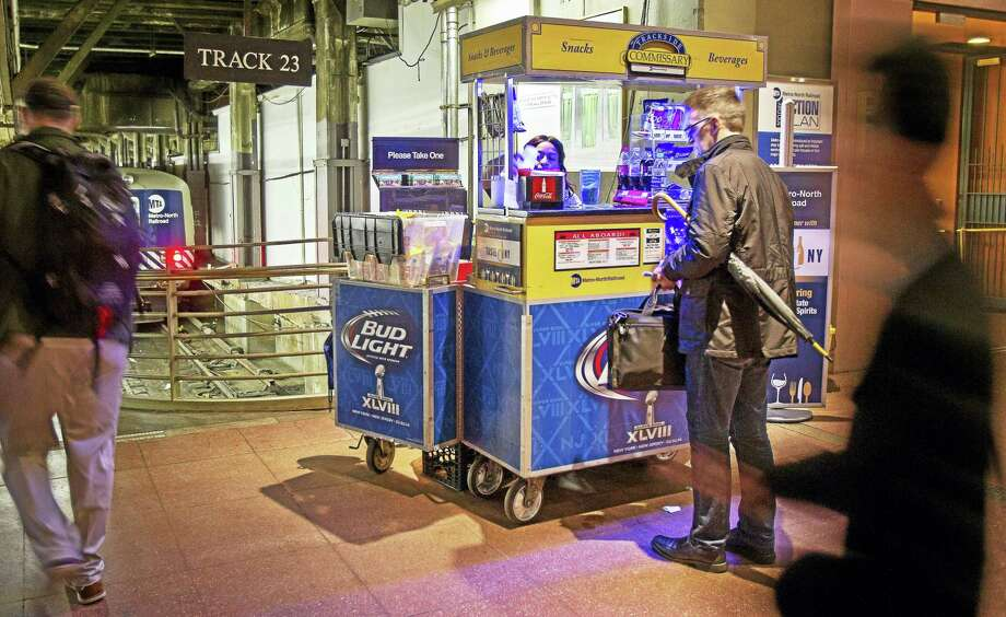 In this 2014 file photo, a commuter buys a beverage from a cart at Grand Central Terminal in New York. If you're taking Metro-North on Thursday to St. Patrick's Day festivities, the railroad says alcoholic beverages will not be allowed on any Metro-North trains or platforms or in any stations. Photo: Associated Press   / AP
