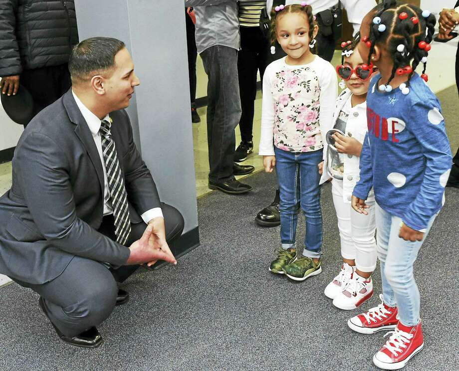 New Haven police Sgt. David Zanelli, left, talks with, from left, Jhi'onna Conyers, 4, and her sister, Madyson Conyers, 3, daughters of Isaiah Conyers, and their cousin, Skye Hines, 5, after a press conference Wednesday announcing charges in the death of Isaiah Conyers. Photo: Peter Hvizdak — New Haven Register   / ©2016 Peter Hvizdak