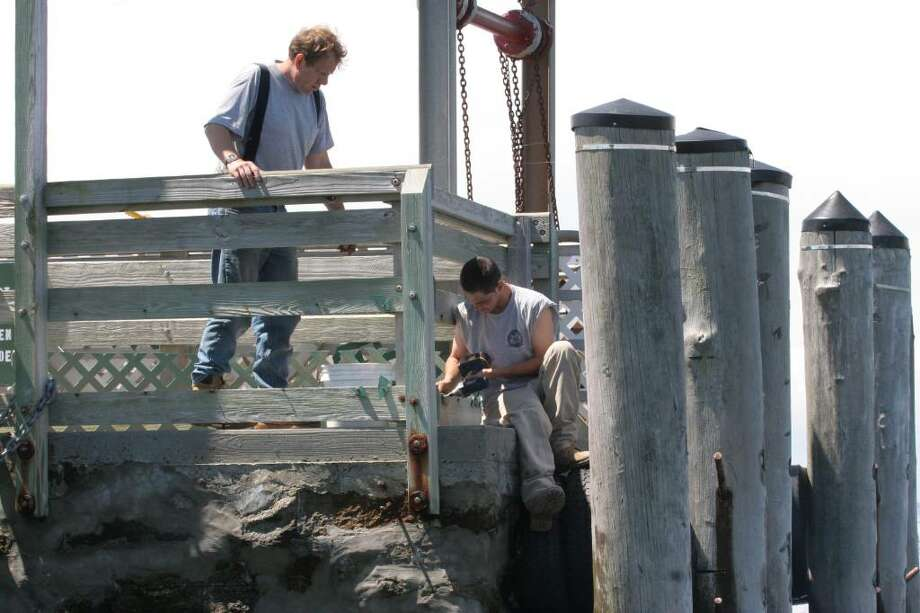 Greenwich Parks Department employees work on the pier at Island Beach in preparation for Saturday's start of seasonal ferry service. Photo: David Ames, David Ames/For Greenwich Time / Greenwich Time