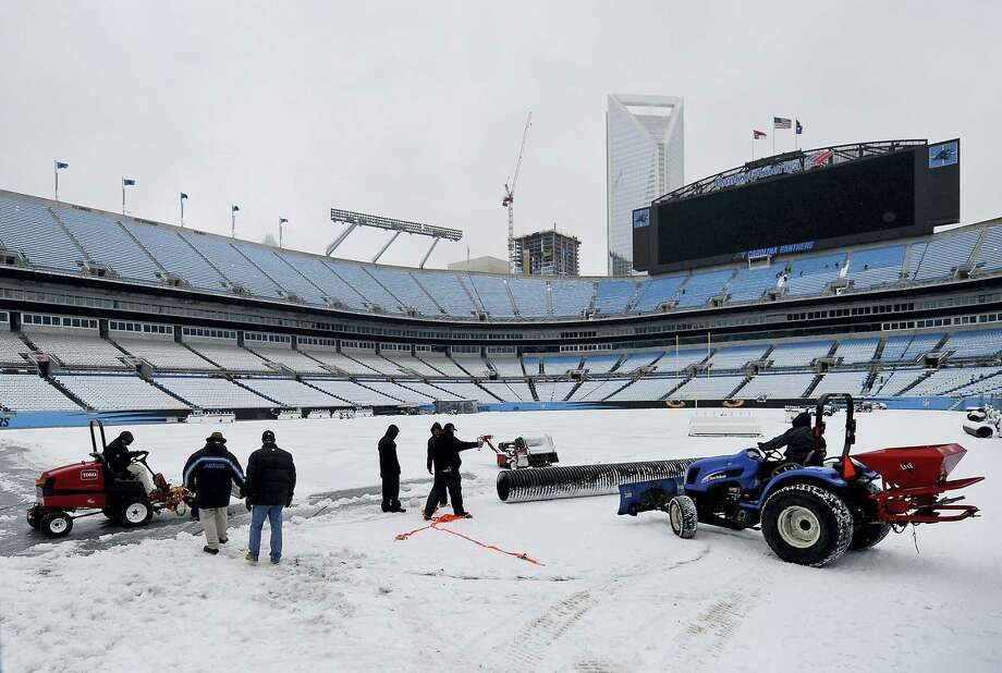 Carolina Panthers personnel work to clear snow and a wintery mix from the tarp covering the field at Bank of America Stadium on Friday in Charlotte, N.C. Photo: Jeff Siner/The Charlotte Observer Via AP   / The Charlotte Observer