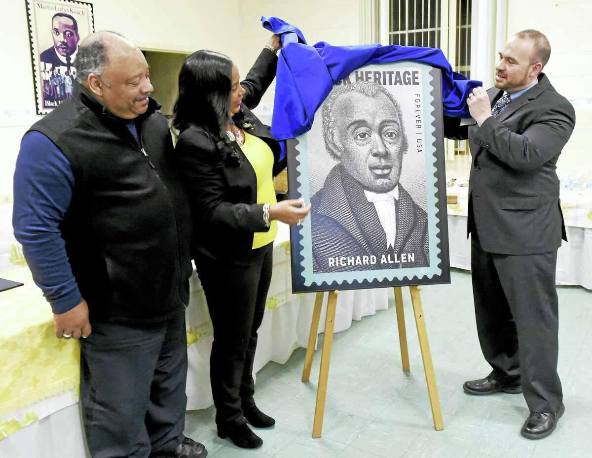 Greater New Haven Branch NAACP First Vice President Anthony Dawson, left, and President Dori Dumas, center, assist New Haven Postmaster Tom Sullivan unveil the USPS 39th commemorative edition Black Heritage stamp of Bishop Richard Allen during a ceremony at St. Luke's Episcopal Church in New Haven Thursday.