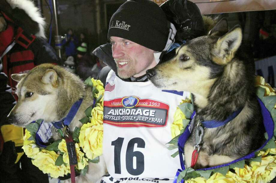 Dallas Seavey poses with his lead dogs Reef, left, and Tide after winning the Iditarod on Tuesday. Photo: Mark Thiessen — The Associated Press   / AP