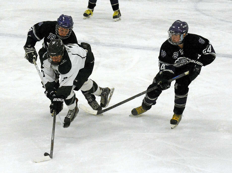 Guilford's Stephen Thibault, center, skates through North Branford's Matt Chamberlain (19) and Dominic Raccio (24). Photo: Dave Phillips — GameTime CT