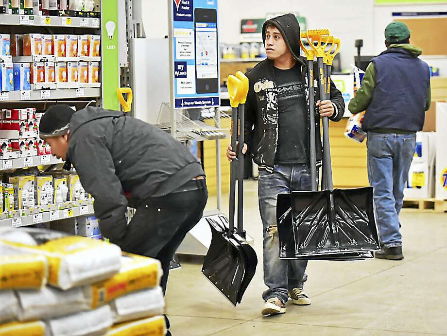 Bryon Diaz, employed by Petiz Landscaping in New Haven, carries five snow shovels at Lowe's on Foxon Blvd. in New Haven, Friday, January 22, 2016, to purchase in preparation for Saturday's forecasted storm. Photo: CATHERINE AVALONE — NEW HAVEN REGISTER