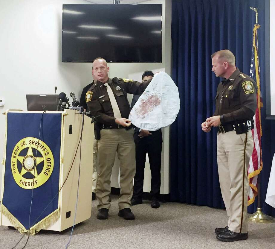 Deputy Danny Beckworth, who investigated the crash site, displays part of a defective airbag believed to have killed 17-year-old Huma Hanif during a news conference April 7 in Houston. The brother of a 17-year-old Texas girl who was killed last week when an exploding Takata air bag sent a shard of metal into her neck said he never received a recall notice about his 2002 Honda Civic. Photo: Emily Foxhall — Houston Chronicle Via AP   / Houston Chronicle