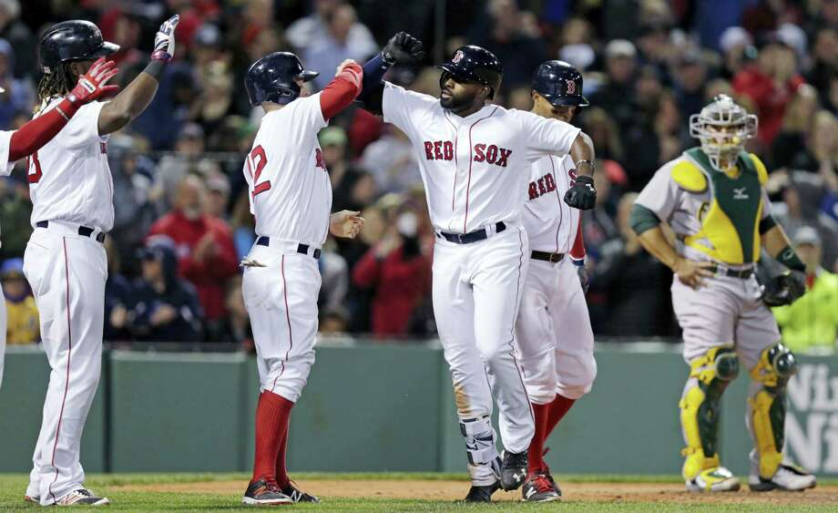Boston Red Sox's Jackie Bradley Jr., center, celebrates after his grand slam during the sixth inning of a baseball game against the Oakland Athletics at Fenway Park in Boston, Monday, May 9, 2016. At right is Oakland Athletics catcher Josh Phegley. (AP Photo/Charles Krupa) Photo: AP / Copyright 2016 The Associated Press. All rights reserved. This material may not be published, broadcast, rewritten or redistribu