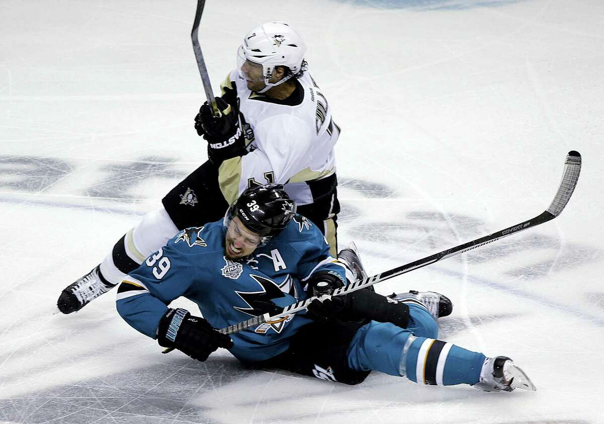 The Penguins' Matt Cullen, top, collides with the Sharks' Logan Couture during the first on Monday.